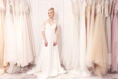 La jeune femme mignonne essaye sur la robe de mariée Images stock