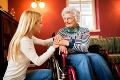 La jeune femme mignonne soulagent sa grand-mère dans le fauteuil roulant Images libres de droits