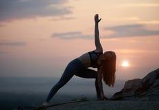 La jeune femme mince attirante faisant le yoga s'exerce dehors sur le fond de l'espace de copie du beau ciel photo stock