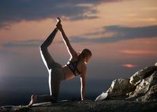 La jeune femme mince attirante faisant le yoga s'exerce dehors sur le fond de l'espace de copie du beau ciel photos stock