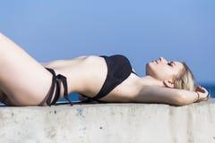 La jeune femme mince dans le bikini la prend un bain de soleil sur le mur en béton image stock