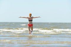 La jeune femme mince exécutant dans la mer ondule images libres de droits