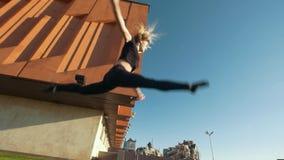 La jeune femme mince exécute le saut acrobatique sur l'herbe sur le paysage urbain de fond banque de vidéos