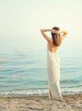 La jeune femme mince s'est habillée dans la longue robe blanche avec le dos nu, reculant avec des mains derrière la tête Photo libre de droits
