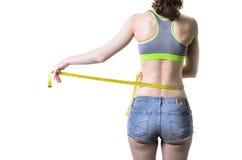 La jeune femme mince se mesure avec une bande de mesure, isolant Photo stock