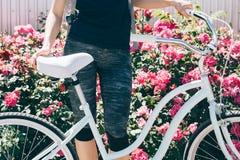 La jeune femme mince se tient avec une bicyclette sur un fond o Images stock