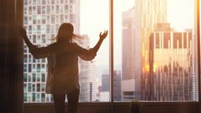 La jeune femme mince se tient prêt la grande fenêtre, étire des mains, se réveillent pendant le matin pendant le lever de soleil photos libres de droits