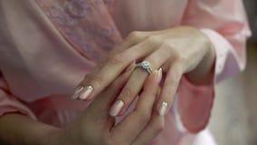 La jeune femme a mis dessus l'anneau sur son doigt banque de vidéos