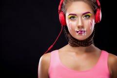 La jeune femme moderne avec le maquillage d'art a plaisir à écouter la musique dans des écouteurs Émotions positives, loisirs Cop Photographie stock