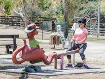 La jeune femme monte sur une oscillation en forme de kangourou au zoo australien Gan Guru dans les kibboutz Nir David, en Israël Image libre de droits