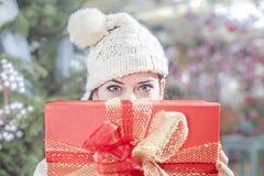 La jeune femme montre ses paquets de cadeau à l'intérieur d'une boutique de Noël Photographie stock libre de droits