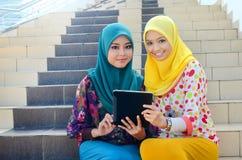 La jeune femme musulmane asiatique dans l'écharpe principale sourient ensemble Images libres de droits