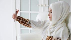 La jeune femme musulmane dans le hijab fait le selfie sur le smartphone se reposant sur le sofa clips vidéos