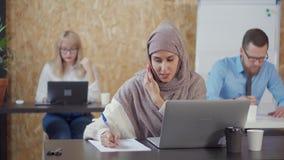 La jeune femme musulmane parle par le téléphone portable dans la pièce contemporaine de bureau banque de vidéos