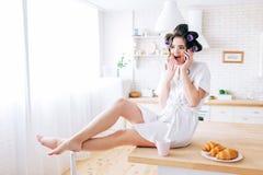 La jeune femme négligente émotive s'asseyent sur la table et l'entretien au téléphone Femme de charge stupéfaite dans la cuisine  image stock