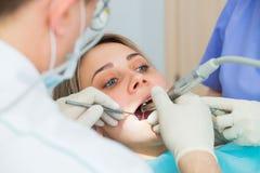 La jeune femme obtenant le plan rapproché dentaire de traitement, les mains du dentiste et l'assistant fait des procédures de tra Photos libres de droits