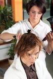 La jeune femme obtient une coiffure dans beauté-font des emplettes Images libres de droits