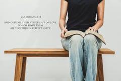 La jeune femme occasionnelle tient un 3h14 ouvert de Colossians de bible sur sa La Image libre de droits