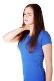 La jeune femme occasionnelle touche son cou. Photos libres de droits