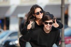 La jeune femme ont l'amusement dehors avec le frère montrant des pouces  Image libre de droits
