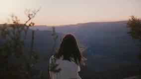 La jeune femme paisible heureuse de vue de dos de mouvement lent avec des cheveux de vol repose le coucher du soleil épique de ob banque de vidéos