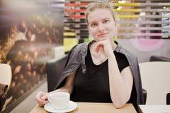 La jeune femme parle au téléphone au café photos stock
