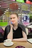 La jeune femme parle au téléphone au café photographie stock libre de droits