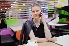 La jeune femme parle au téléphone au café photos libres de droits