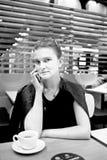 La jeune femme parle au téléphone au café image libre de droits