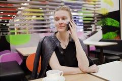 La jeune femme parle au téléphone au café images stock