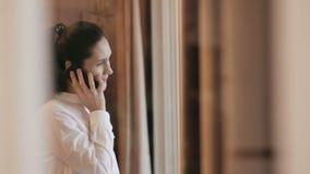 La jeune femme parle au téléphone près de la fenêtre banque de vidéos