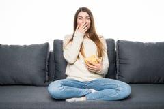 La jeune femme passe son temps gratuit regardant la TV sur le divan à la maison, mâchant des puces Image libre de droits