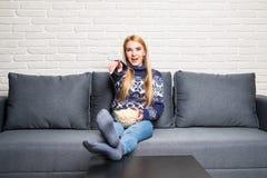 La jeune femme passe son temps gratuit regardant la TV sur le divan à la maison, mâchant le maïs éclaté Image stock
