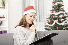 La jeune femme pensent à Noël avec la liste Photographie stock libre de droits