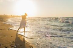 La jeune femme a plaisir à marcher sur une plage floue au crépuscule Photo stock
