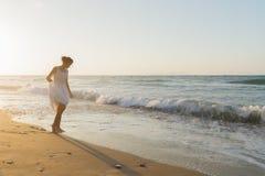 La jeune femme a plaisir à marcher sur une plage floue au crépuscule Photographie stock