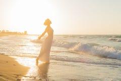 La jeune femme a plaisir à marcher sur une plage floue au crépuscule Image stock