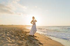 La jeune femme a plaisir à marcher sur une plage floue au crépuscule Image libre de droits