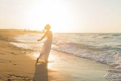 La jeune femme a plaisir à marcher sur une plage floue au crépuscule Photographie stock libre de droits