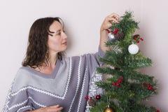 La jeune femme près a décoré l'arbre de Noël photos libres de droits