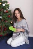 La jeune femme près a décoré l'arbre de Noël photos stock