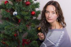 La jeune femme près a décoré l'arbre de Noël images libres de droits
