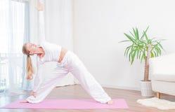 La jeune femme pratique le yoga à la maison sur le tapis, fille faisant l'exercice d'Utthita Trikonasana, pose prolongée de trian photos stock