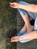 La jeune femme pratique le yoga et médite en position de lotus Photographie stock