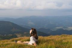 La jeune femme prend le dessus de repos de la colline en montagnes carpathiennes et écoute musique dans des écouteurs appréciant  Photographie stock libre de droits