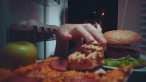 La jeune femme prend la nourriture du réfrigérateur la nuit banque de vidéos