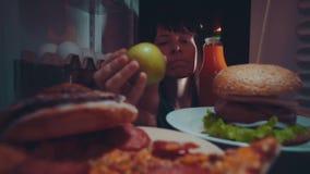 La jeune femme prend la nourriture du réfrigérateur la nuit clips vidéos