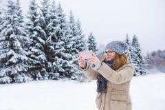 La jeune femme prend la photo sur un fond de forêt couverte de neige d'hiver Photos stock