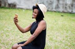 La jeune femme prend un autoportrait avec son téléphone portable photos stock