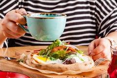 La jeune femme prend un petit déjeuner anglais traditionnel avec le lard et les oeufs images libres de droits